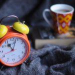 un réveil, une tasse et un livre : tout pour avoir un sommeil réparateur