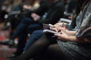 Personnes prenant des notes sur un cahier posé sur leurs genoux