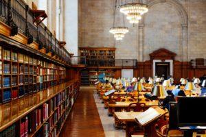 Une bibliothèque universitaire avec ses étagères et ses pupitres alignés