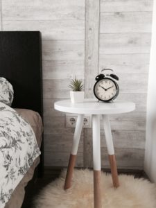 réveil posé sur une table de chevet avec un cactus près d'un lit