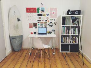 Un espace bureau bien organisé avec un moodboard fait de collages pour rester motivé