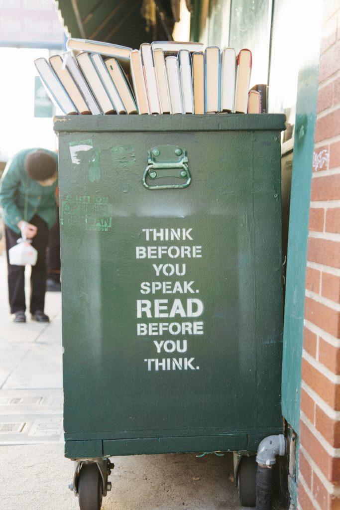 """un poubelle sur le couvercle de laquelle des livres sont posés. Une inscription indique """"Pense avant de parler. Lit avant de penser"""""""