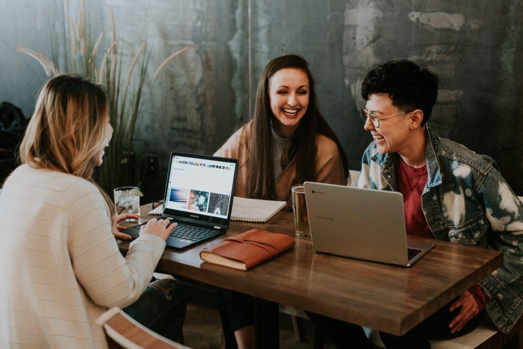 3 personnes travaillant en groupe dans un café