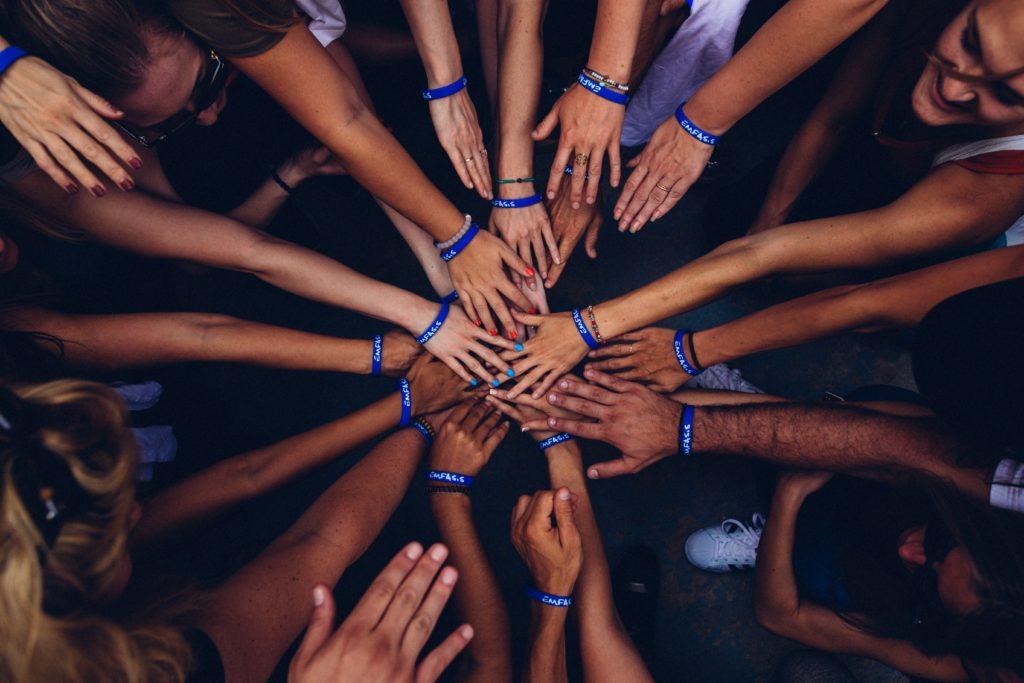 Mains réunis symbolisant l'entraide, une des valeurs du travail de groupe