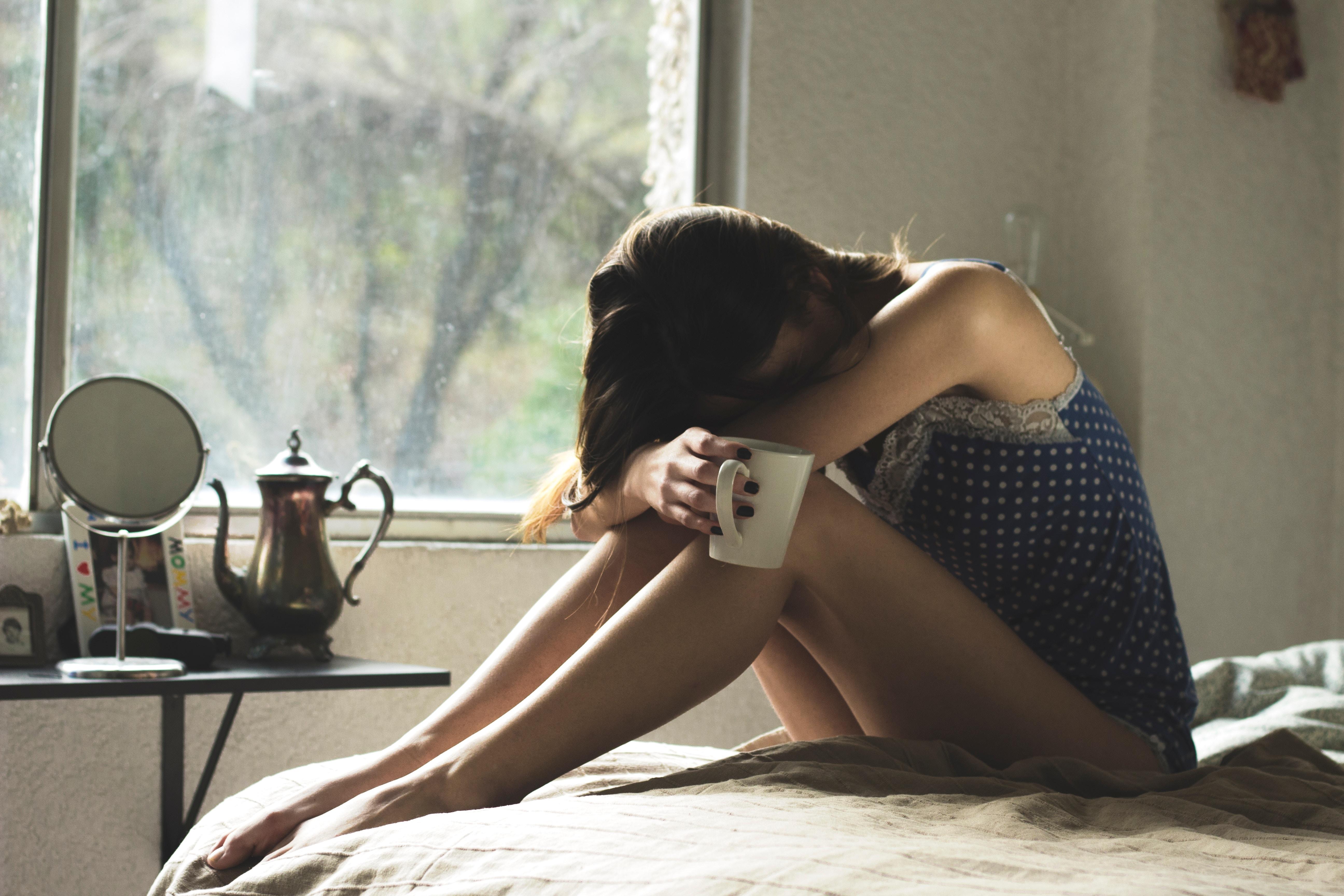 jeune fille tête baissée sur ses genoux, prostrée, dans une attitude de burn-out étudiant