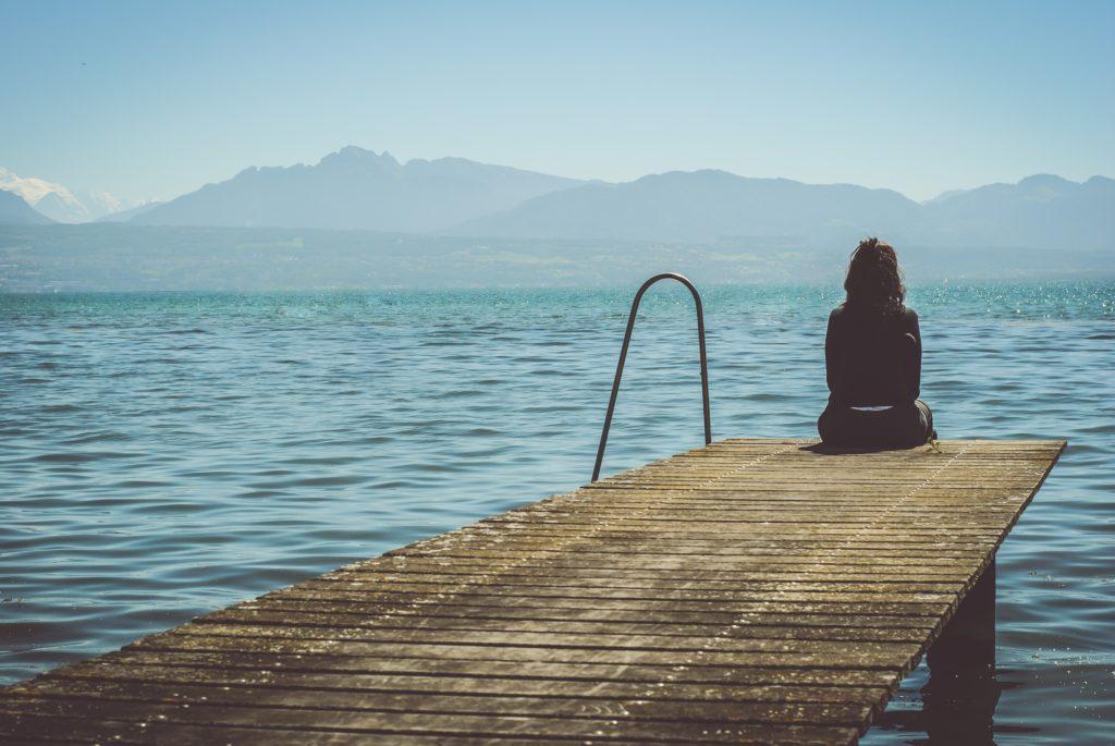 une personne de dos sur un ponton regardant le lac et les montagnes