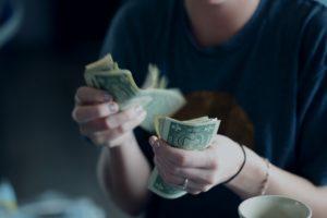 personne comptant des billets de banque pour établir son budget étudiant