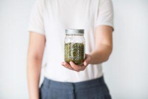personne tendant un pot en verre contenant des lentilles