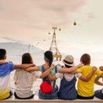 personnes de dos assises se tenant par les épaules devant un paysage