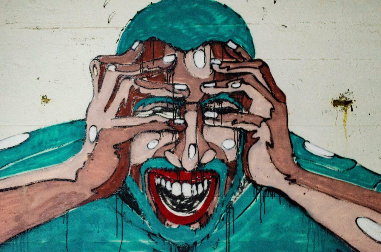 graffiti représentant un homme se tenant le visage