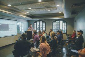 Personnes écoutant un exposé oral avec une présentation