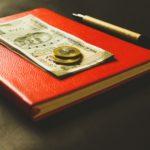 un cahier rouge sur lequel est posé un billet et 2 pièces de monnaies